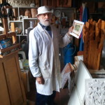 Il maetro Lino Tinè nel suo studio con la foto della sua vetrata